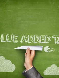 Value added tax concept on blackboard with paper plane